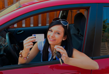 Young Female Driver Holding Hey Car Keys and Drivers License